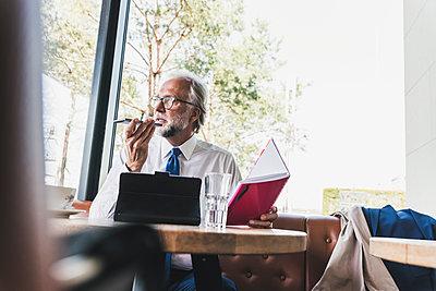 Mature businessman working at table in a cafe - p300m1587443 von Uwe Umstätter