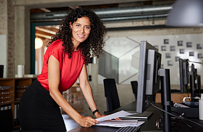 Smiling businesswoman holding document while leaning on desk - p300m2293750 by Rainer Berg