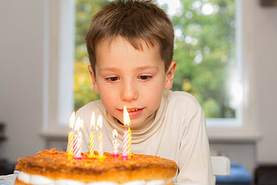 Cute birthday boy looking at candles on cake - p301m1101891f by Sven Hagolani