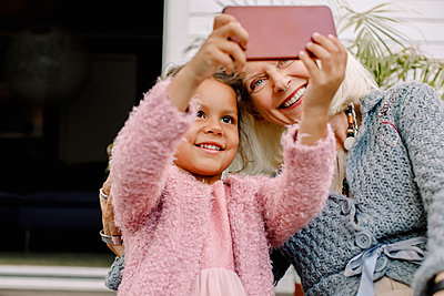 Smiling granddaughter and grandmother taking selfie in mobile phone - p426m2159689 by Maskot