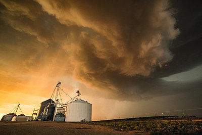 Strong storm above the town of Dalhart with strong winds, heavy rain and hail, grain silo in the foreground, Dalhart, Texas, USA - p429m1494494 by Jessica Moore