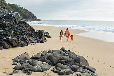 Caucasian mother and children walking on beach - p555m1305336 by Marc Romanelli