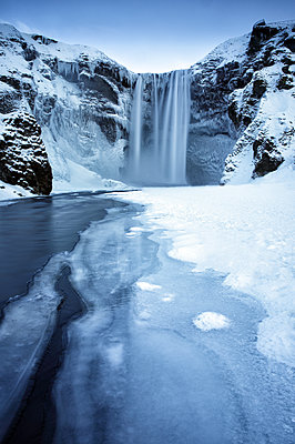 Winter view of Skogafoss waterfall, with cliffs covered in icicles and foregreound covered in snow, Skogar, South Iceland, Polar Regions - p871m1506631 by Lee Frost