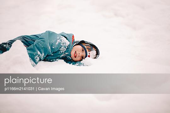 Happy boy lying in snow during winter - p1166m2141031 by Cavan Images