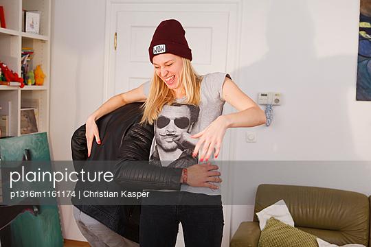 Junges Paar albern im Wohnzimmer herum - p1316m1161174 von Christian Kasper