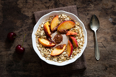 Cherry smoothie bowl with peach and oat flakes, topping - p300m1166589 by Eva Gruendemann