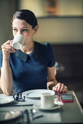 Young woman drinking coffee in a cafe - p300m1189526 by A. Tamboly