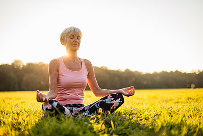 Senior woman in lotus position on rural meadow at sunset - p300m2058671 by Daniel Ingold