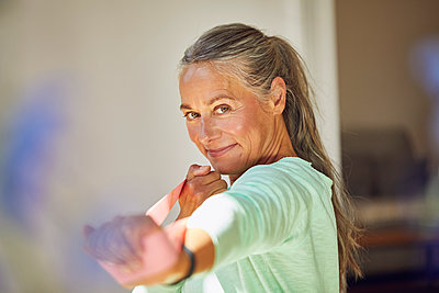Smiling woman exercising with resistance band at home - p300m2206866 by Maya Claussen
