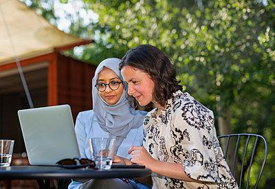 Female friends using laptop in garden - p312m2237127 by Pernille Tofte