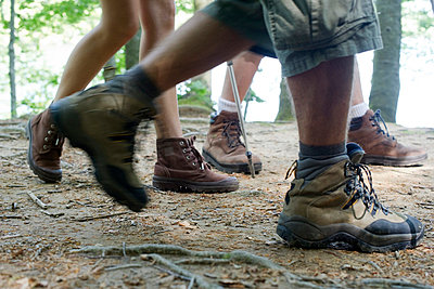 Hikers hiking in woods, low section - p623m699793f by Frederic Cirou