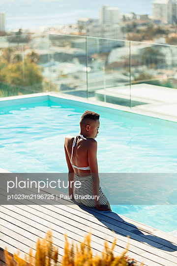 Serene young woman at sunny rooftop swimming pool - p1023m2196725 by Paul Bradbury