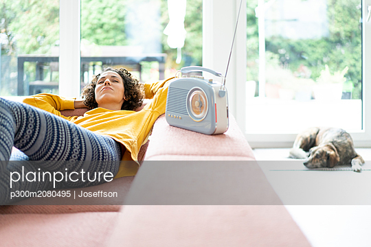 Woman lying on couch listening to music with portable radio at home - p300m2080495 by Joseffson