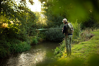 Man with backpack fly fishing at riverbank - p1023m2262044 by Martin Barraud