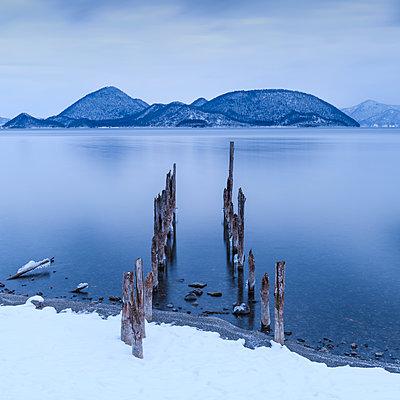 Long exposure shot of wooden sticks in the water at lake Toya, Hokkaido, Japan - p1166m2108033 by Cavan Images