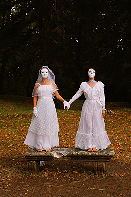 Brides with white masks on a bench in the forest - p1521m2214998 by Charlotte Zobel