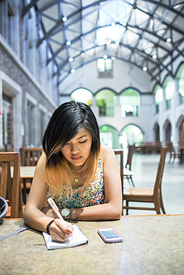 Chinese woman sitting in library writing in notebook - p555m1301978 by Take A Pix Media