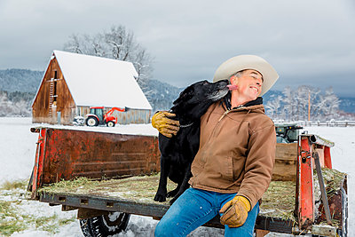 Dog licking face of Caucasian farmer in snowy truck - p555m1312056 by Inti St Clair