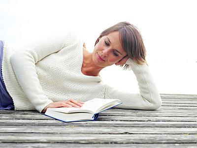 Frau liest Buch auf einem Steg  - p6430084 von senior images