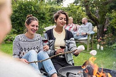 Friends roasting marshmallows - p788m1165407 by Lisa Krechting