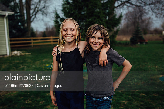 boy and girl with big smiles posing for camera - p1166m2279627 by Cavan Images