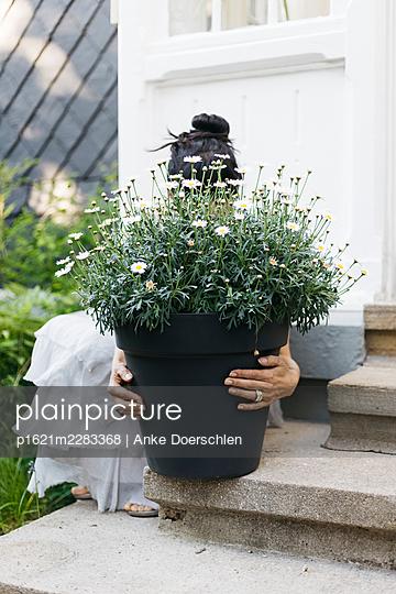 Woman behind flower pot - p1621m2283368 by Anke Doerschlen