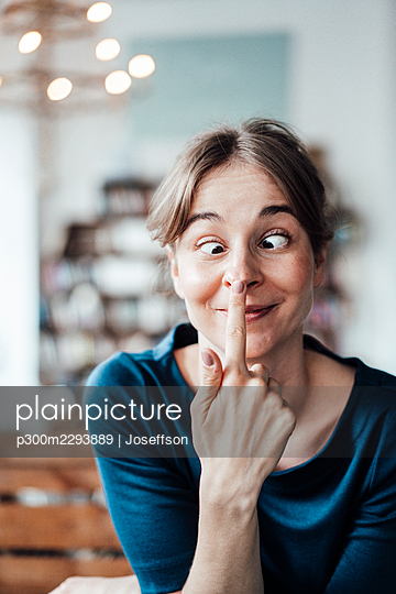 Young woman touching nose while making face in cafe - p300m2293889 by Joseffson