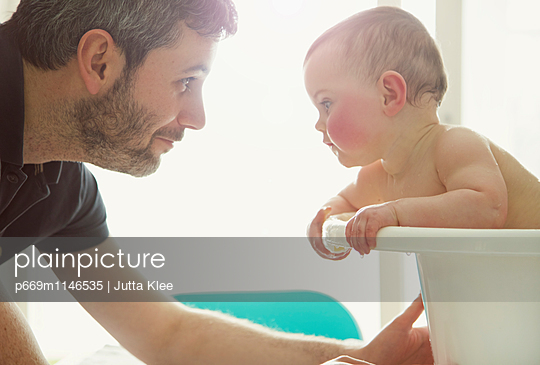 Father Bathing Baby Girl - p669m1146535 by Jutta Klee photography