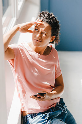 Woman holding smartphone, twinkling in sunlight - p300m2012736 von Kniel Synnatzschke