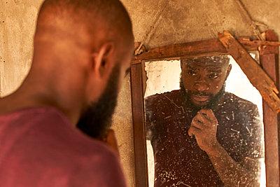 Mozambique, Maputo, young man watching his mirror image - p300m2104185 von Veam