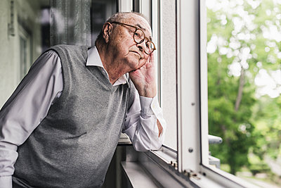 Portrait of sad senior man looking out of window - p300m2189524 by Uwe Umstätter