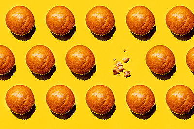 Pattern of rows of muffins against yellow background with single one missing - p300m2198482 by Gemma Ferrando