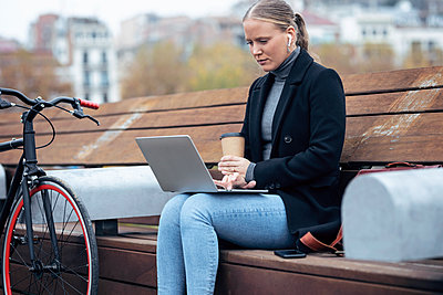 Woman holding coffee cup while using laptop on bench by bicycle - p300m2256032 by Josep Suria