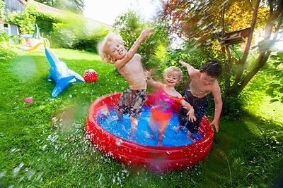 Children splashing in paddling pool - p429m712193f by jackSTAR
