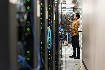 Hispanic technician working in computer server room - p555m1305047 by Jetta Productions