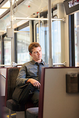 Mid adult office worker looking bored on train journey - p924m895667f by heshphoto