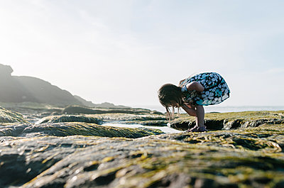 Girl searching something while bending over rocks against clear sky - p1166m1474547 by Cavan Images