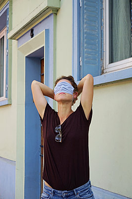 A woman covers her eyes with a cloth mask - p1610m2209943 by myriam tirler