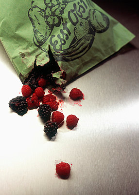 Berries spilling out of a ripped paper bag - p30110978f by Ludger Paffrath