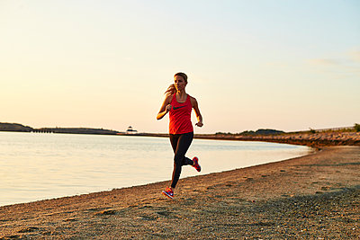 A young athletic woman runs along the beach. - p343m1184162 by Josh Campbell