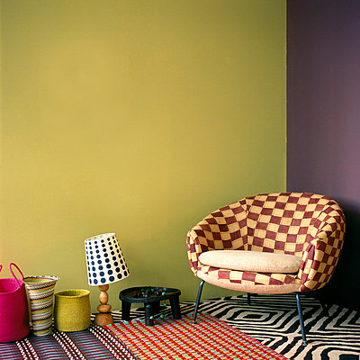 Living room with checked patterned armchair painted walls patterned carpet with rugs and and colourful home wares - p349m695180 by Emma Lee