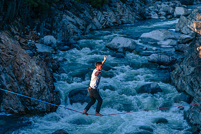 Man highlining above river, Truckee, California, USA - p429m2023093 by Alex Eggermont