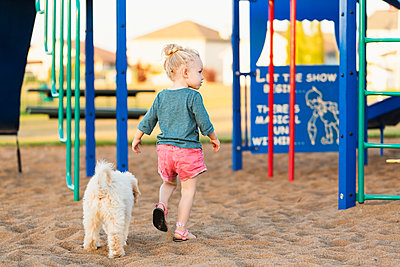 A young girl and her pet dog playing in a playground on a warm fall day; Spruce Grove, Alberta, Canada - p442m2004256 by LJM Photo