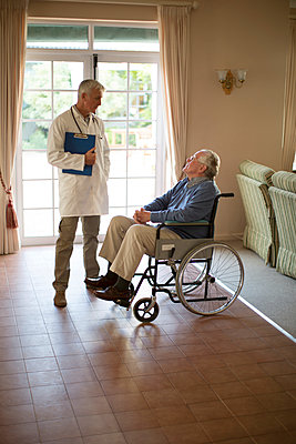 Doctor talking to patient in wheelchair - p555m1305755 by Resolution Productions