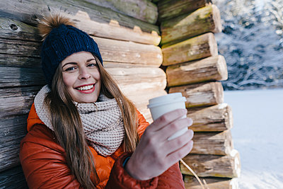 Young woman in winter clothing at log cabin - p586m2005079 by Kniel Synnatzschke