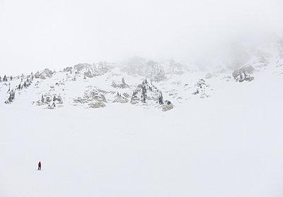 Lone skier in white mountain landscape - p92411930 by Samantha Mitchell