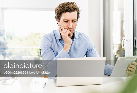 Mid adult man using digital tablet while sitting in office - p300m2226623 by Uwe Umstätter