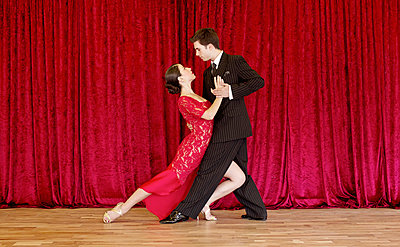 Tango dancers against red curtain - p1445m2128306 by Eugenia Kyriakopoulou