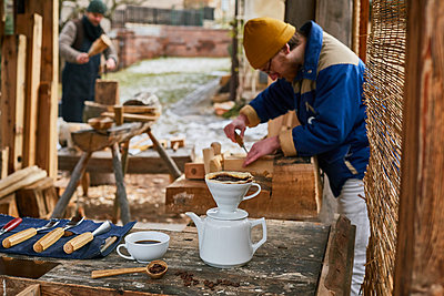 Coffee break in the wood workshop in the open air - p1573m2175262 by Christian Bendel