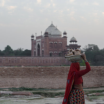 Woman carries stones on her head, mosque in the background - p1624m2223742 by Gabriela Torres Ruiz